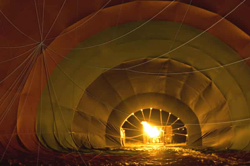 Inflating hot balloon at dawn in the bush